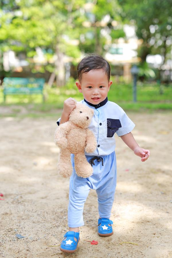 Happy toddler boy walking outside with holding teddy bear in the park outdoor.  royalty free stock image