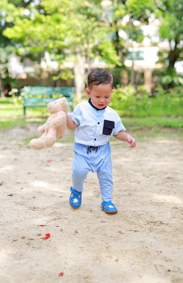 Happy toddler boy walking outside with holding teddy bear in the park outdoor.  stock photo