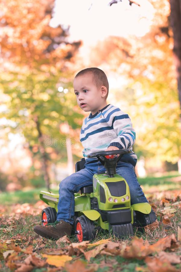 Happy toddler driving a toy truck stock images