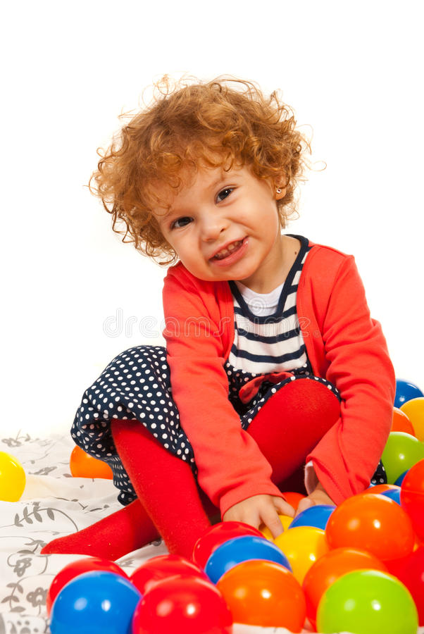 Happy toddler girl with colorful balls stock photos