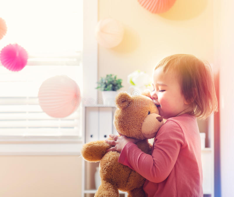 Happy toddler girl playing with her teddy bear royalty free stock photography