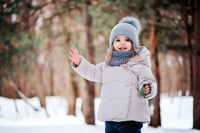 Happy toddler girl playing in winter forest with snow royalty free stock image