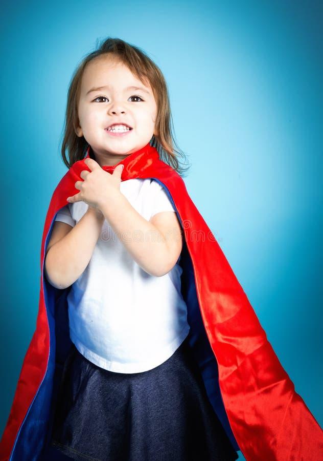 Happy toddler girl in a super hero cape. Happy toddler girl playing in a super hero cape stock images