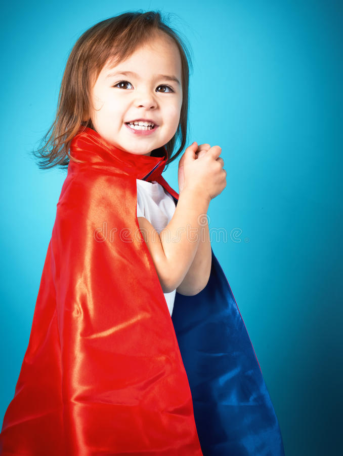 Happy toddler girl in a super hero cape. Happy toddler girl playing in a super hero cape royalty free stock photography