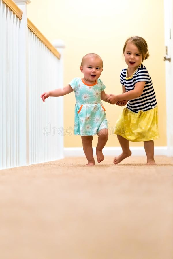 Happy toddler girls running and playing stock photography