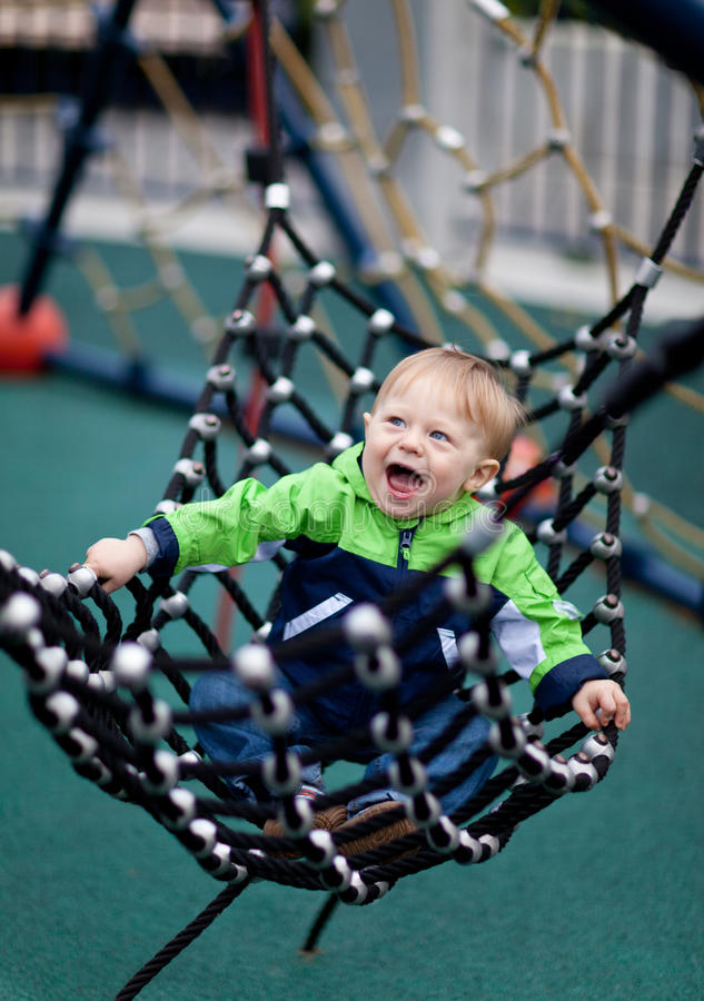 Happy toddler in a hammock at a playground royalty free stock photos