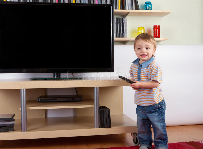 Happy toddler with remote control in front of the TV royalty free stock photo