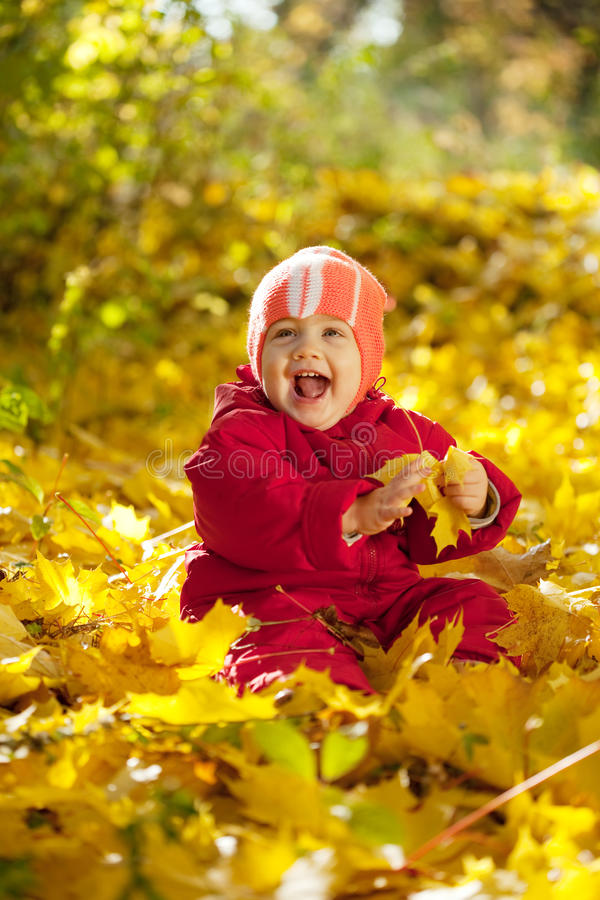 Happy toddler sitting on maple leaves stock photos
