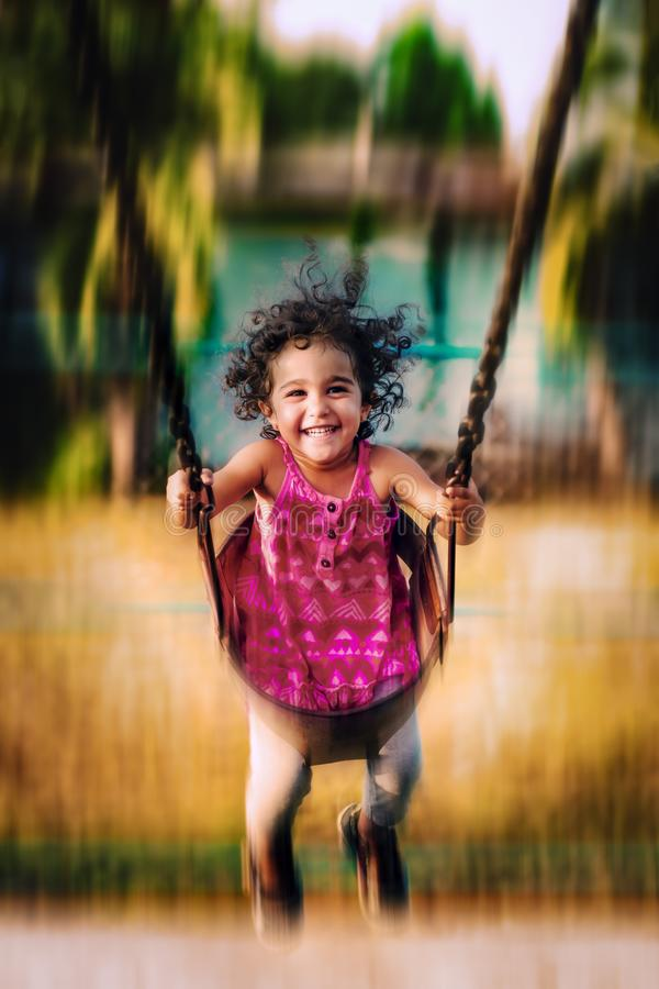 Happy toddler swinging high happy and joyful playing in the park having fun outdoors royalty free stock photo