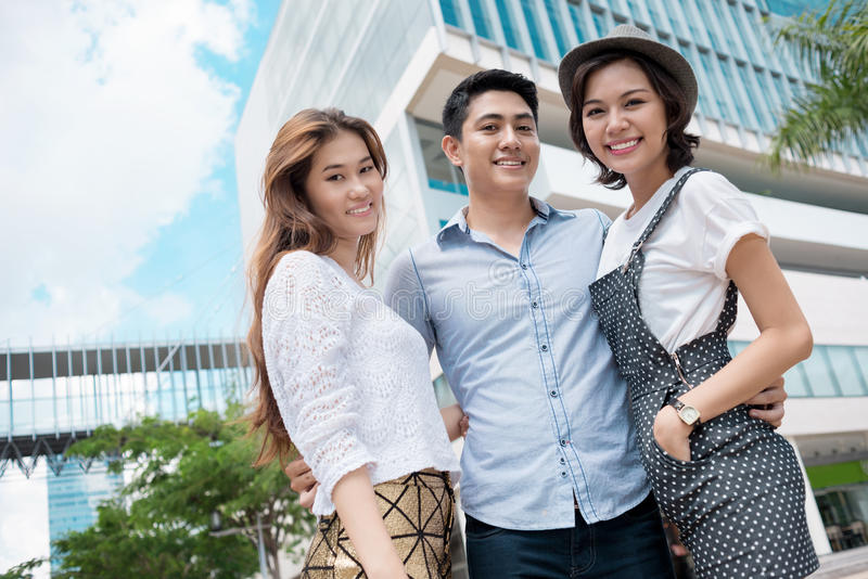 Happy together. Angle view of friends standing in front of a modern building royalty free stock photography
