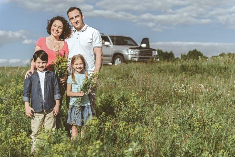 Joyful family standing on meadow near car stock photography