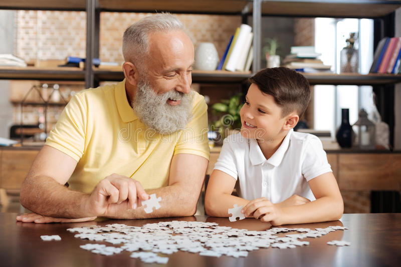 Grandfather and grandson smiling at each other while doing puzzle royalty free stock photography
