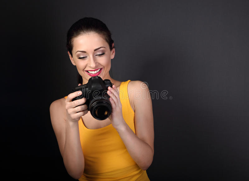 Happy toothy smiling young female photograph in yellow top holding camera and looking on photo on dark background royalty free stock photo