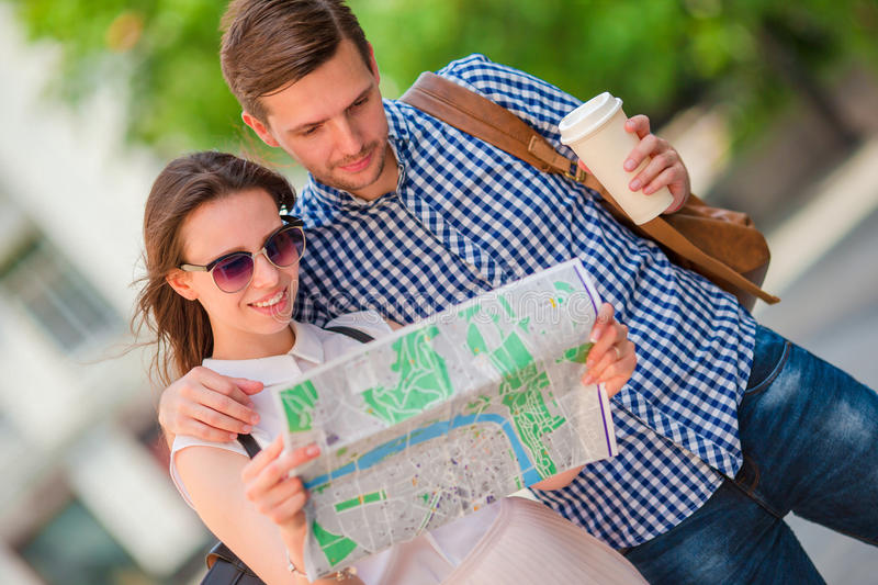 Happy tourist couple traveling in Europe smiling happy. Caucasian friends with city map in search of attractions. Young. Happy tourist couple, men and women stock images
