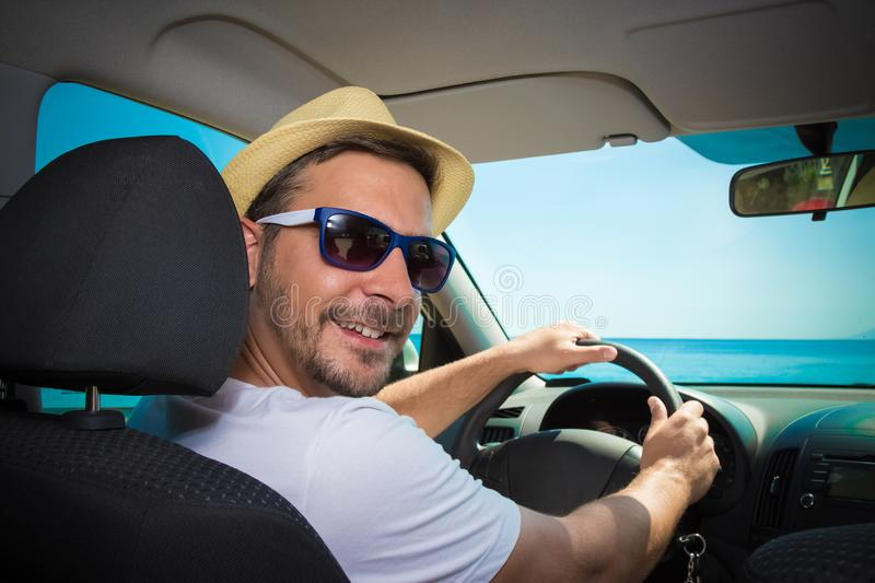 Portrait of tourist guy in car. Travel and summer vacation concepts. royalty free stock image