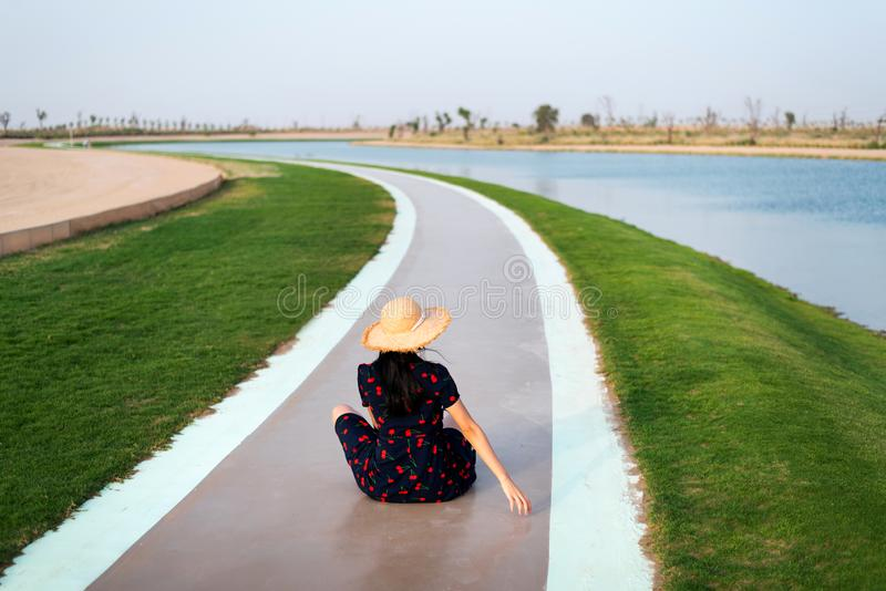 Happy tourist enjoying Love lakes in Dubai. Happy tourist enjoying Love lakes view in Dubai, woman, heart, girl, shape, female, sitting, boardwalk, wanderlust royalty free stock photos
