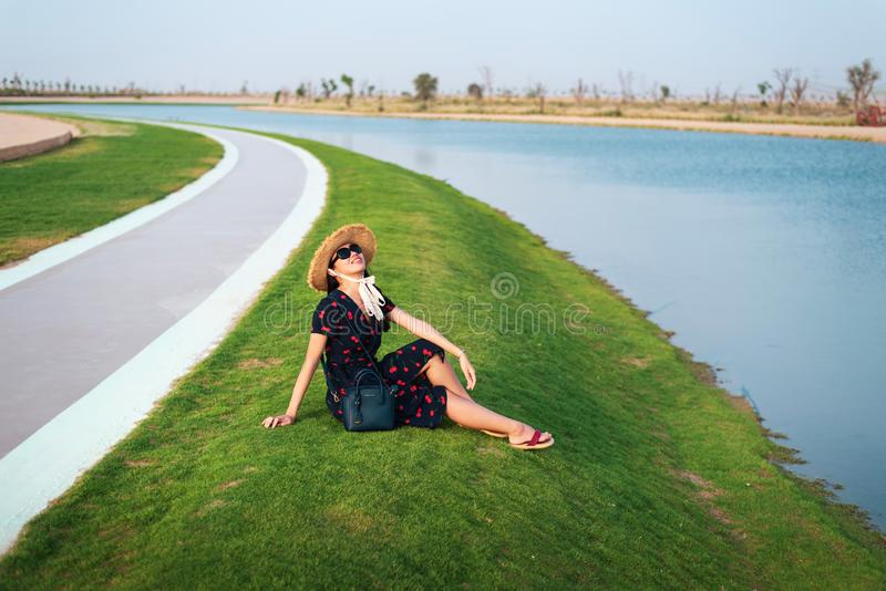 Happy tourist enjoying Love lakes in Dubai. Happy tourist enjoying Love lakes view in Dubai, woman, heart, girl, shape, female, sitting, boardwalk, wanderlust stock photo