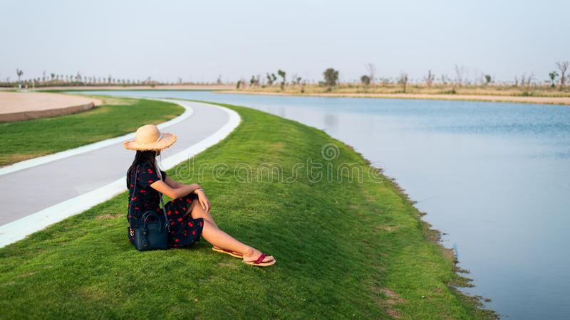 Happy tourist enjoying Love lakes in Dubai. Happy tourist enjoying Love lakes view in Dubai, woman, heart, girl, shape, female, sitting, boardwalk, wanderlust royalty free stock photography