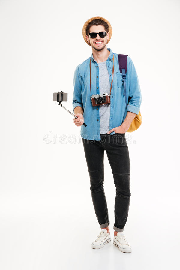 Happy tourist holding backpack, camera and smartphone on selfie stick. Happy young tourist holding backpack, vintage camera and smartphone on selfie stick over stock photography