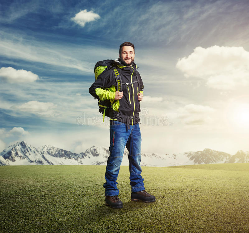 Happy tourist with knapsack. Smiling and looking at camera over beautiful landscape royalty free stock photography