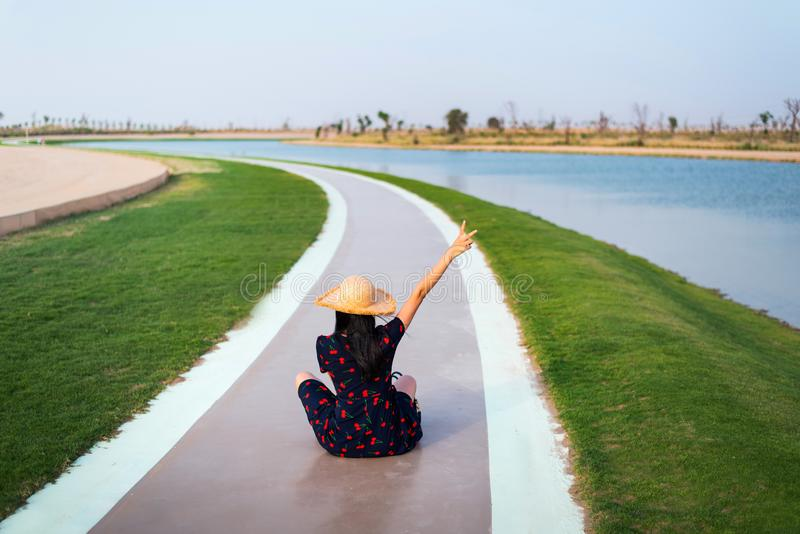 Happy tourist at Love lakes in Dubai. UAE, woman, girl, heart, shape, female, wanderlust, asian, water, chinese, people, travel, visit, grass, emirate, united royalty free stock images