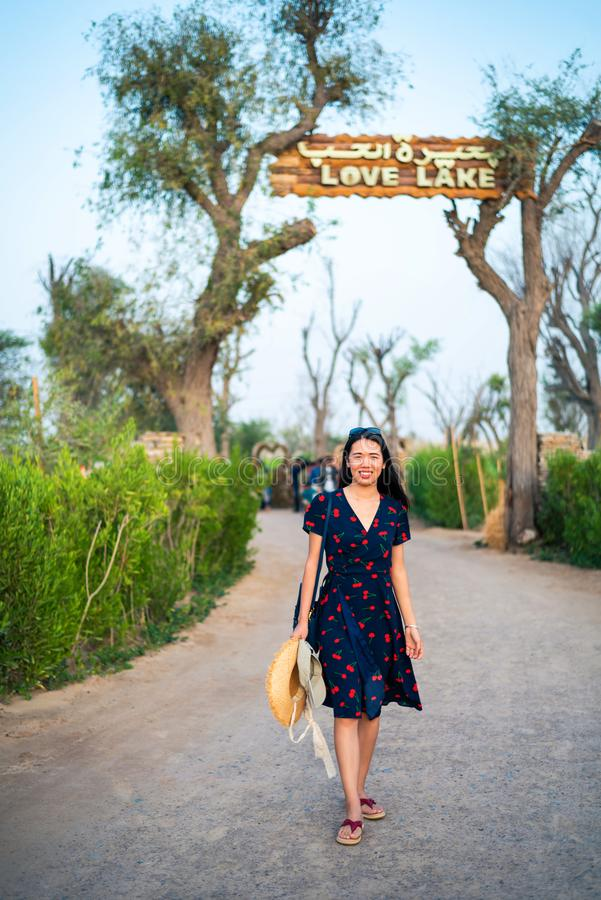 Happy tourist at Love lakes entrance in Dubai. Happy tourist at Love lakes entrance gatet in Dubai, woman, girl, heart, shape, asian, female, wanderlust, people stock photography