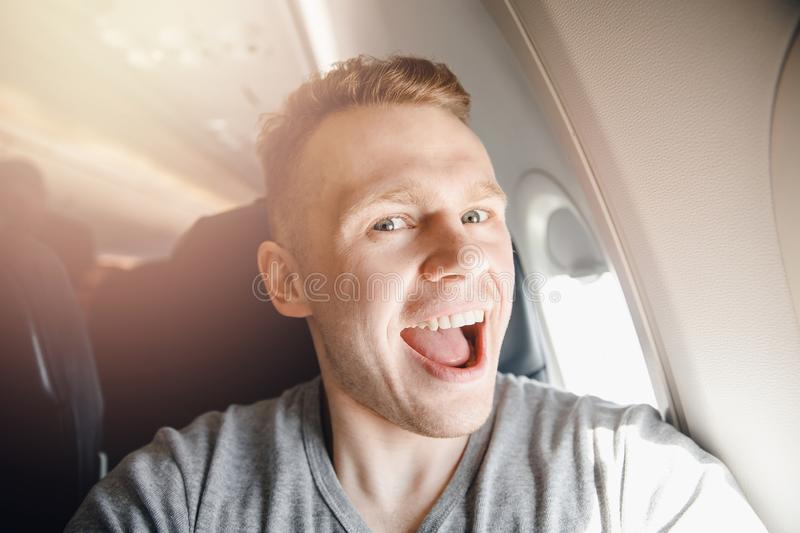 Happy tourist man makes selfie photo in cabin aircraft airplane before departure. Travel concept stock photography