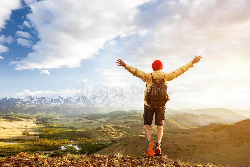 Happy tourist man raised arms against sunset mountains stock images