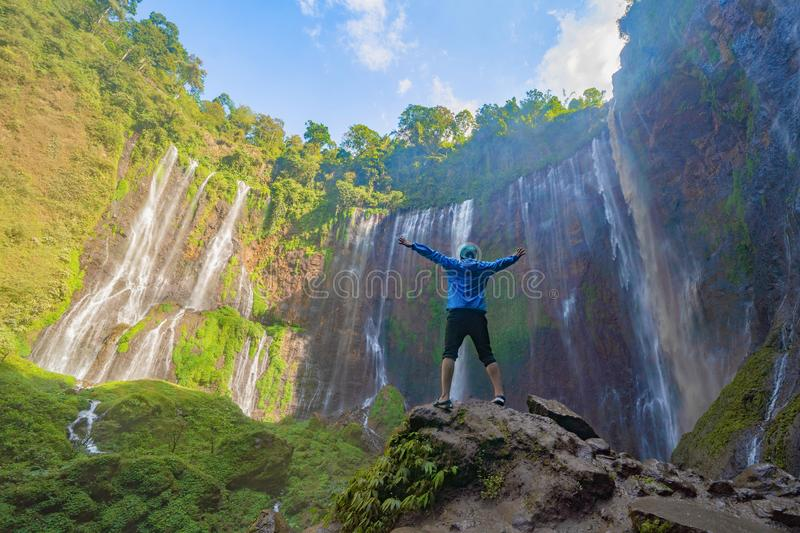 A happy tourist man watching Sewu Waterfall. The biggest waterfall in Java Island. Nature landscape background of travel trip and royalty free stock photography