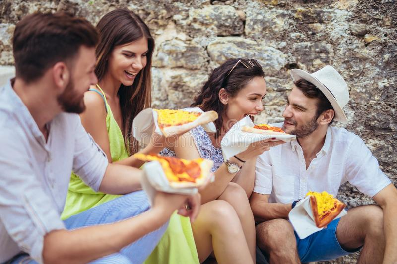 Happy people eating fast food in city while travelling. Happy tourist people eating fast food in city while travelling stock photos