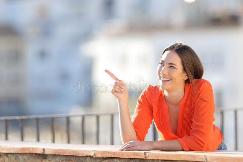 Happy tourist pointing at side in a balcony royalty free stock photography