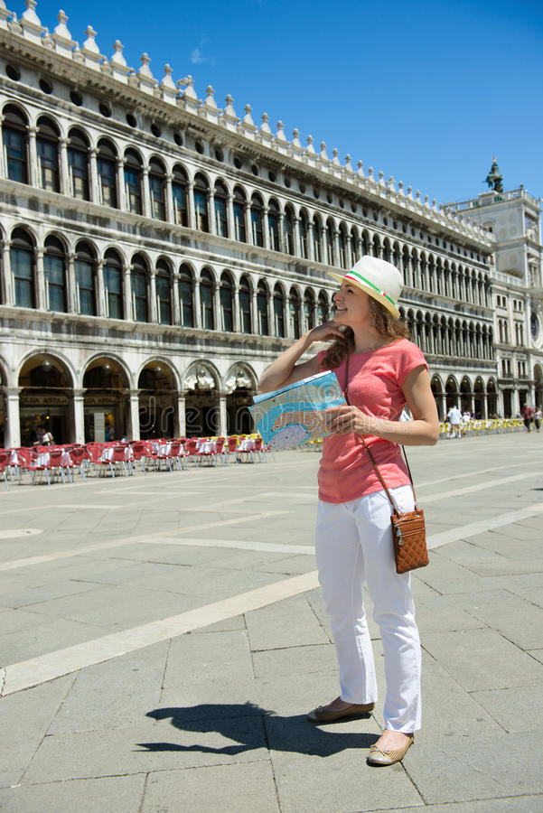 Happy tourist at San Marco square in Venice. Happy tourist girl with map at San Marco square in Venice stock photo