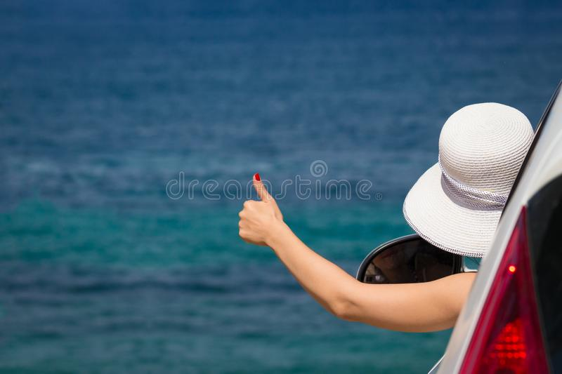 Rear view of female tourist in car showing thumbs up. Blue sea i stock image