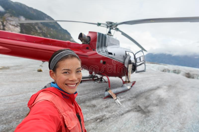 Happy woman taking selfie on helicopter excursion stock photography