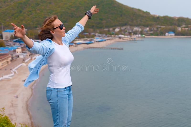 Happy tourist woman climbed to the top of the mountain. Emotions of joy and happiness. Mountain and sea in the background. Close. Up stock images