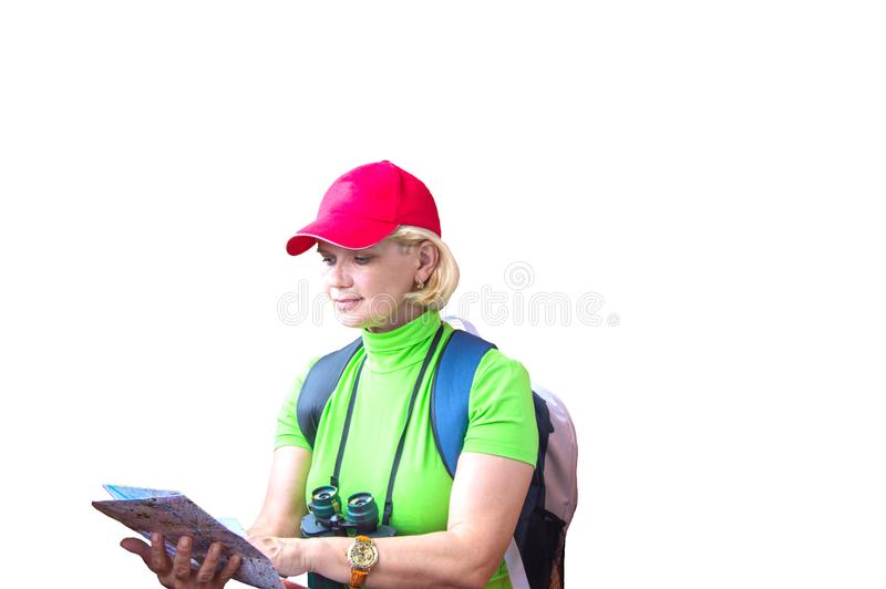 Happy tourist woman in green t-shirt and red cap with backpack looking at map isolated on white background royalty free stock photography