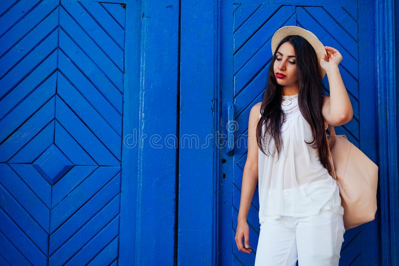 Happy tourist woman smiling against blue wooden door. Outdoor portrait of beautiful college girl wearing summer outfit stock photo