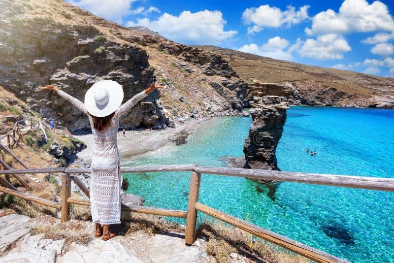 A tourist woman in a white dress enjoys the view to the famous beach of Tis Grias to Pidima, Andros, Greece stock photo