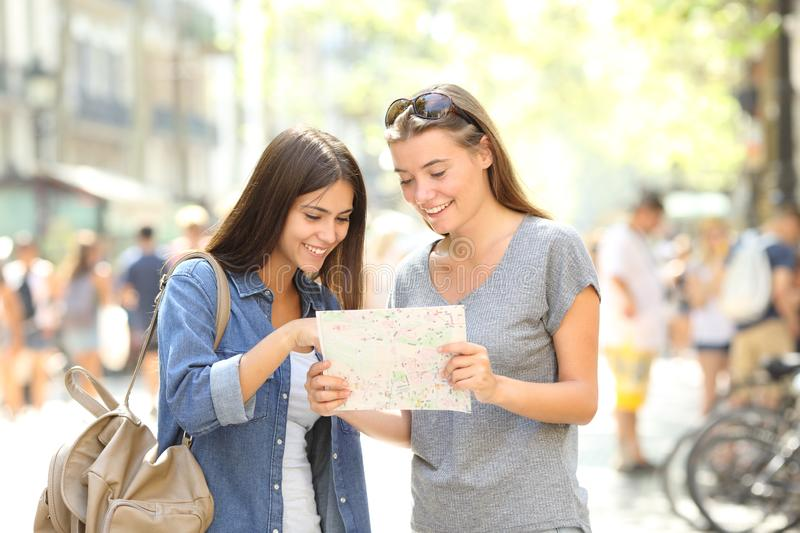 Happy tourists checking paper guide in the street stock photos