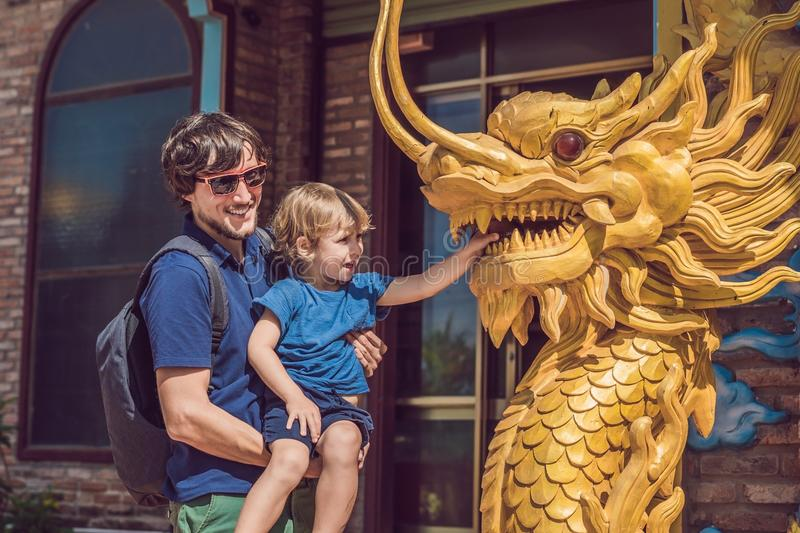 Happy tourists dad and son watching Asian dragon. Travel to Asia concept. Traveling with a baby concept stock image