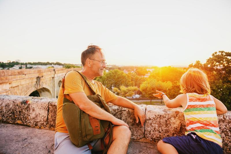 Happy tourists, father and son enjoying sunset at Saint Clement Aqueduct in Montpellier royalty free stock image