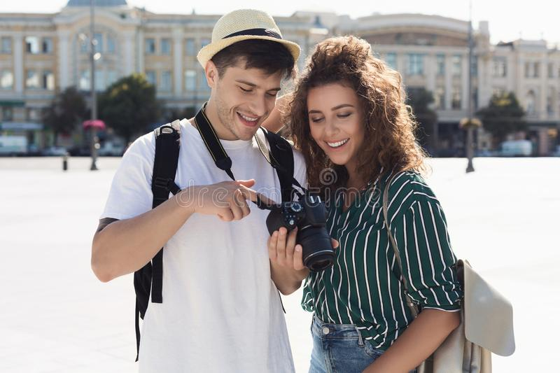 Happy tourists looking at photos on camera stock photo