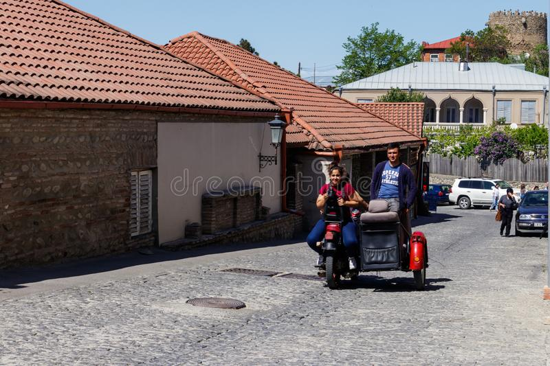 Happy tourists riding all terrain vehicle on street of the medieval town Sighnaghi. Sighnaghi, Kakheti, Georgia - May 2, 2018: Happy tourists riding all terrain stock images