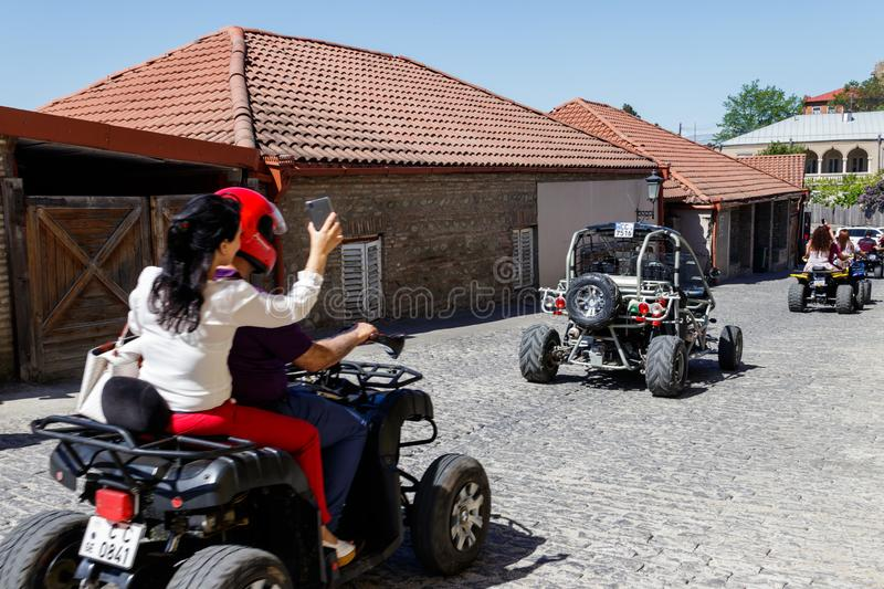 Happy tourists riding all terrain vehicle on street of the medieval town Sighnaghi. Sighnaghi, Kakheti, Georgia - May 2, 2018: Happy tourists riding all terrain stock photos