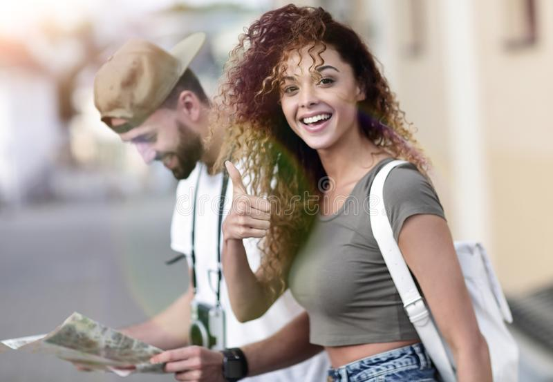 Happy tourists taking a walk in a city street in a sunny day stock photos