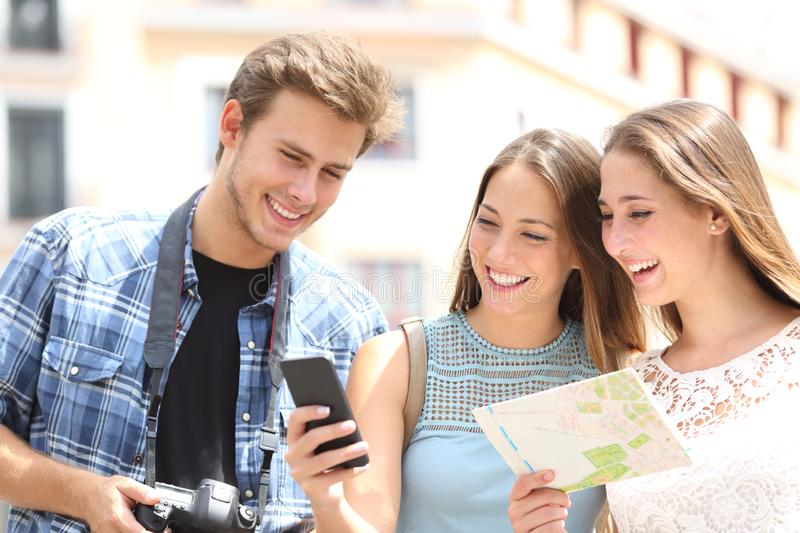 Happy tourists traveling checking phone and map stock images