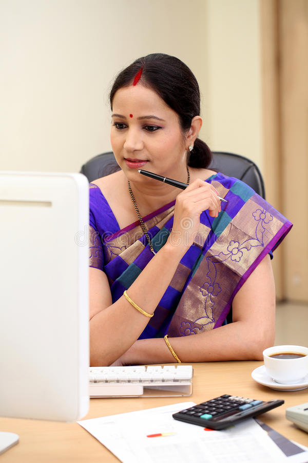 Happy traditional Indian business woman at office desk royalty free stock photo