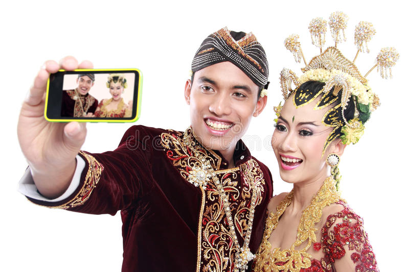 Download Happy Traditional Java Wedding Couple With Mobile Phone Stock Image - Image: 30829899