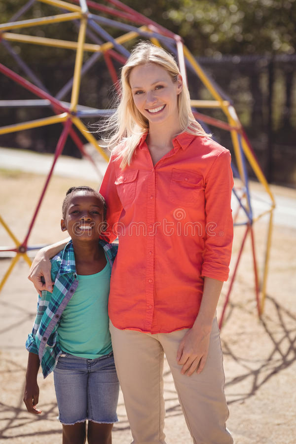 Happy trainer and girl standing together at school playground stock photo