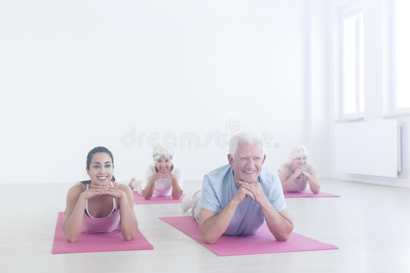 Elderly people lying on mats stock images